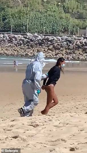 Female surfer is dragged away by hamzat-officials and arrested on Spanish beach after going in the sea while infected with COVID-19 (photos)