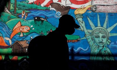 A man in a mask walks in front of a mural in New York