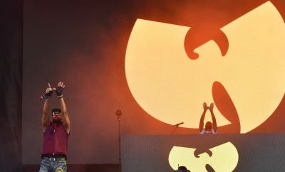 RZA performs in front of a Wu-Tang Clan sign