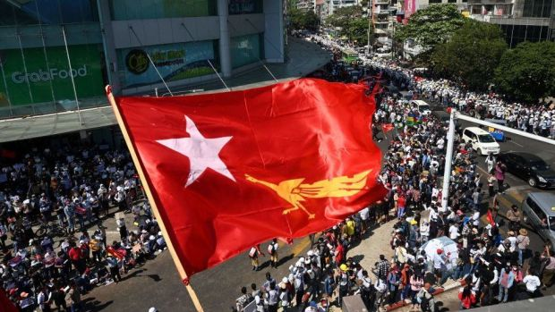 The flag of the National League for Democracy party flies over protesters taking part in a demonstration against the February 1 military coup in Yangon