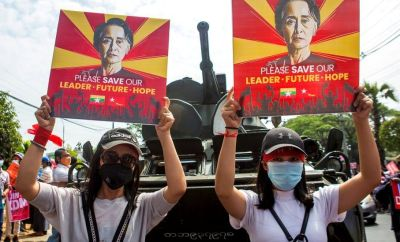 Demonstrators hold placards with the image of Aung San Suu Kyi during a protest against the military coup, outside the Central Bank of Myanmar in Yangon, 15 February 2021