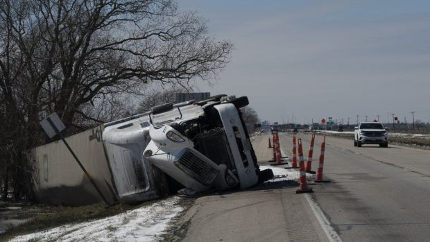 A large trailer truck is seen flipped sideways on highway 59 in Texas