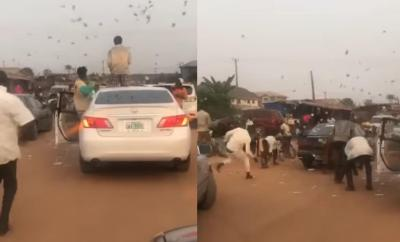 Alleged Yahoo Boys cause traffic as they stop in middle of the road to throw money in the air in Benin (video)