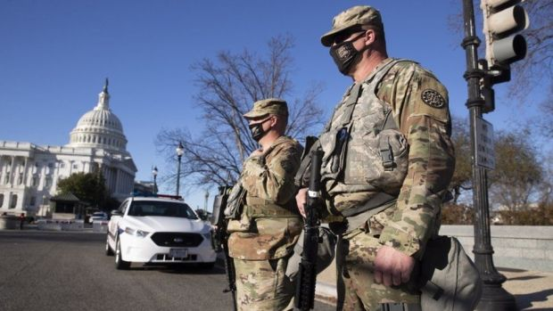 Members of the National Guard stand at the East Front of the US Capitol in Washington, DC