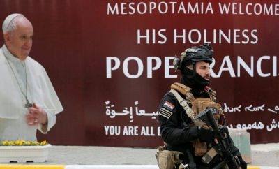 Security officer walks near a poster of Pope Francis in Baghdad ahead of his visit to Iraq (4 March 2021)