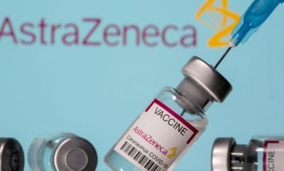 """Vials labelled """"Astra Zeneca COVID-19 Coronavirus Vaccine"""" and a syringe are seen in front of a displayed AstraZeneca logo, in this illustration photo taken March 14, 2021."""