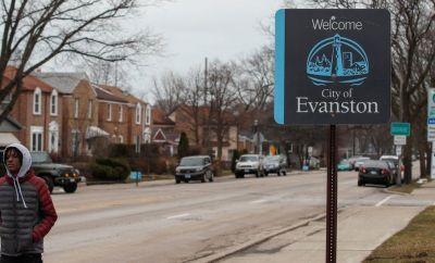A man walks by a sign welcoming people to the city of in Evanston, Illinois, on March 16, 2021