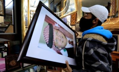 A frame maker in a frame shop displays pictures of King Abdullah II bin Al-Hussein king of Jordan, in Amman, Jordan, 4 April