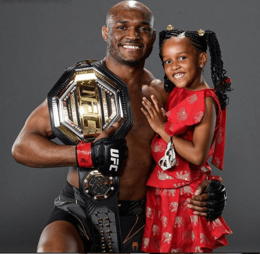 Cute photo of Kamaru Usman and his daughter posing with his belt following his recent win against Jorge Masvidal.