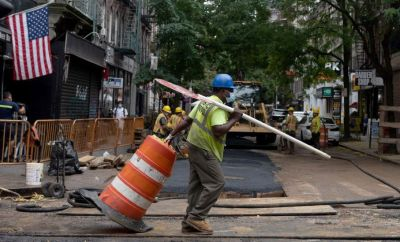 Construction worker drags cone