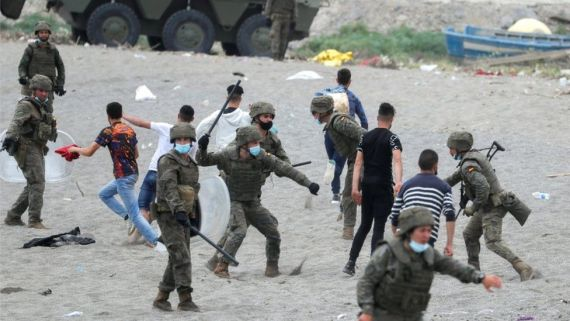 A Spanish legionnaire hits a Moroccan citizen at El Tarajal beach, near the fence between the Spanish-Moroccan border