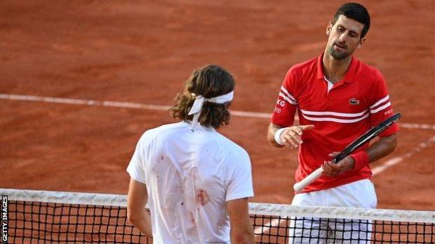 Djokovic shakes hands with Tsitsipas at the net