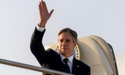 Antony Blinken waves as he exits his plane