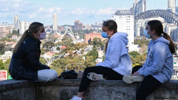 Three girls wearing face masks sit above the Bradfield Highway in the suburb of Sydney, Australia. Photo: 7 July 2021