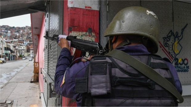 A member of the Bolivarian National Police aims at a possible target after clashes with alleged members of a criminal gang at the Cota 905 neighborhood, in Caracas on July 9, 2021.