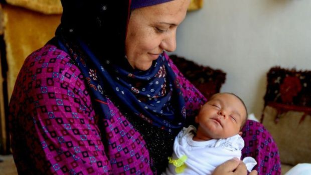 A Syrian refugee holds her newborn girl in Beirut
