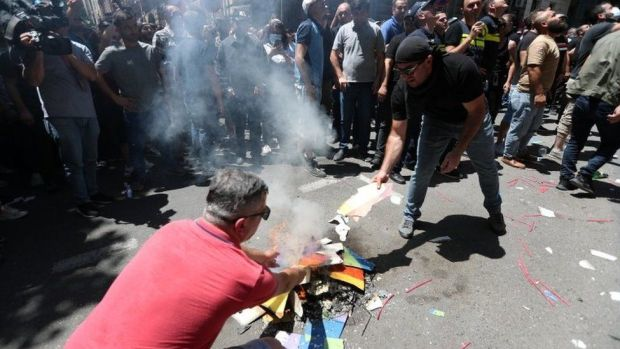 Protesters burn the rainbow flag during a protest in Georgia