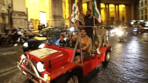 Italy fans celebrate as they drive in a car in Naples. Photo: 11 July 2021