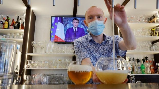 A man pours a beer in a bar while President Macron is on the TV behind him.