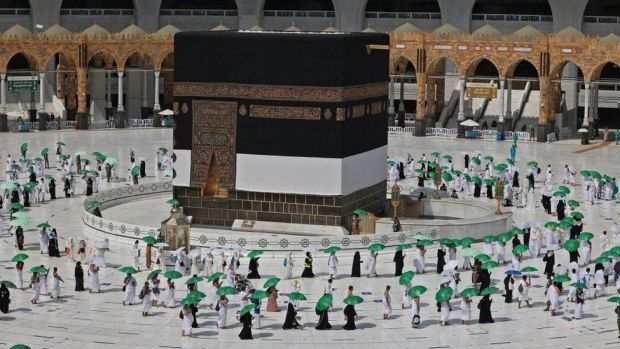 Pilgrims holding umrellas to protect themselves from the heat, arrive at the Kaaba, Islam's holiest shrine, at the Grand mosque in the holy city of Meccca