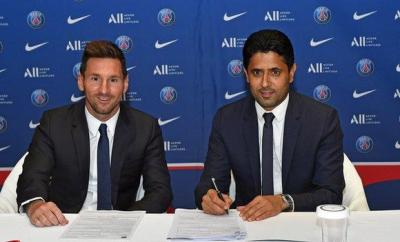 Lionel Messi signing his PSG contract with club president Nasser al-Khelaifi