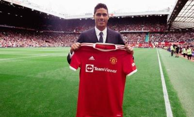 Raphael Varane poses on the Old Trafford pitch with his Manchester United shirt