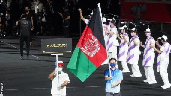 A volunteer carries the Afghan flag at the Tokyo Paralympics opening ceremony