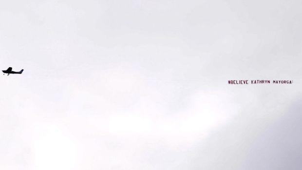 "A banner reading ""#Believe Kathryn Mayorga"" flies over the stadium"