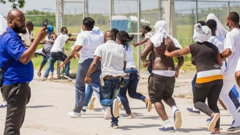 Haitian migrants try to return to the airplane used by U.S. authorities to fly them out of a Texas border city after crossing the Rio Grande river from Mexico, at Toussaint Louverture International Airport in Port-au-Prince, Haiti September 21, 2021.