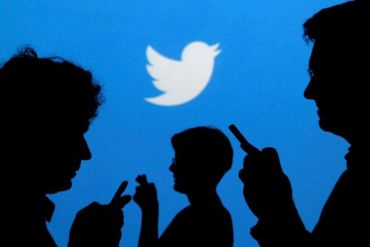 Silhouettes look at phones with the Twitter logo in the background