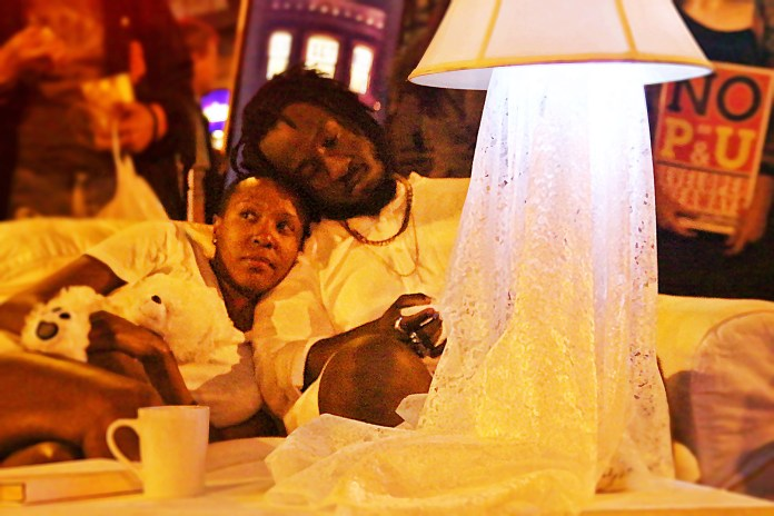 Mustafah Greene & April Martin, from San Francisco Anti-displacement Coalition,  sit on a sofa in their make shift home at the intersection of Mission and 22nd. Actors engaged in performance art as the occupied the space. Photo by Sana Saleem