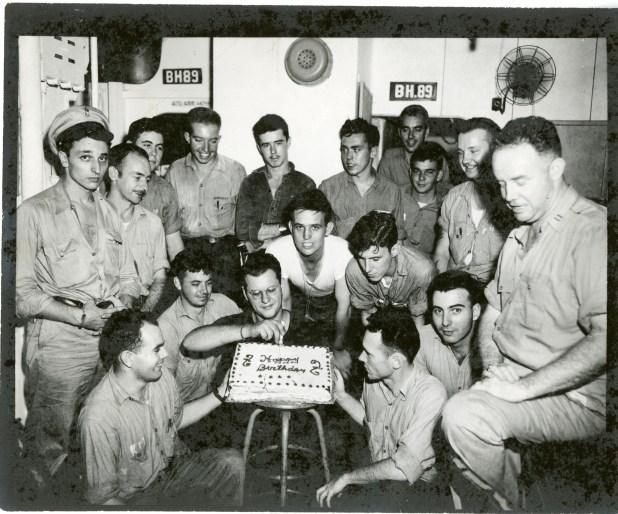 Uniformed sailors posing with birthday cake aboard the USS Hancock ...
