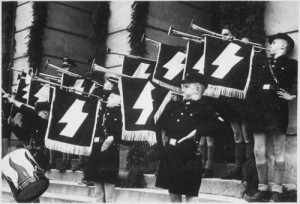 Hitler Youth Hour of Commemoration in front of the Town Hall in Tomaszow, Poland during German-Nazi occupation, May 11, 1941. Photo: US National Archives and Records Administration via Wikimedia Commons.