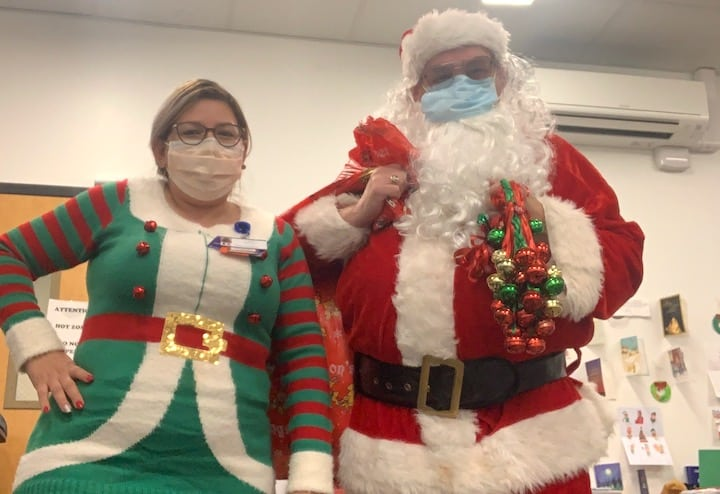 [CREDIT: CNE] Dick Oakley (Santa/pharmacist) and Cindy Santana (Elf/Pharmacy technician) visited the COVID-19 Field Hospital in Cranston to hand out gifts bags filled with get well/holiday cards, crossword puzzles, and decks of playing cards donated from the community.