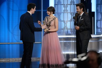 """Damien Chazelle accepts the Golden Globe from Felicity Jones for BEST SCREENPLAY – MOTION PICTURE for """"La La Land"""" at the 74th Annual Golden Globe Awards at the Beverly Hotel in Beverly Hills, CA on Sunday, January 8, 2017."""
