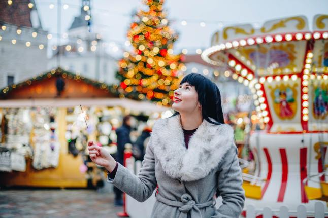woman-standing-near-carnival-rides-and-christmas-tree
