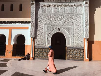 person-walking-beside-mosque