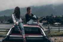 two-women-sitting-on-vehicle-roofs