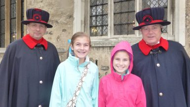 Two Beefeaters at the Tower of London pose with two girls
