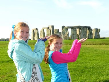 Two girls posed like they are holding Stonehenge in the palms of their hands