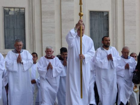 Man in white robe carrying staff leads procession into St. Peter's Basilica