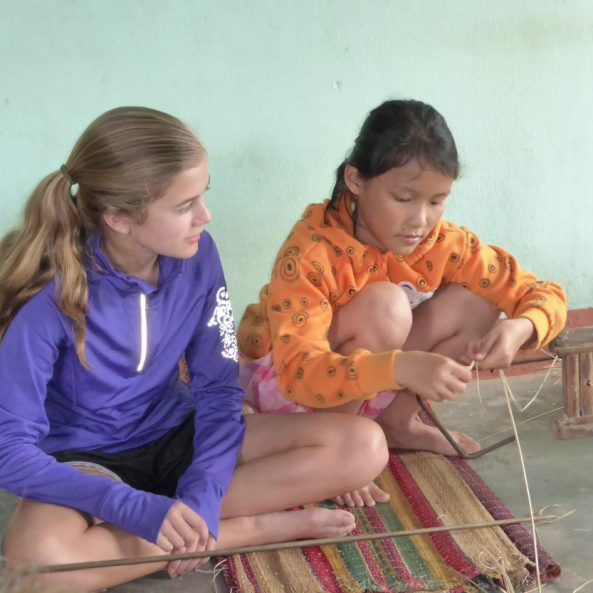 Vietnamese girl teaches American girl how to weave mats