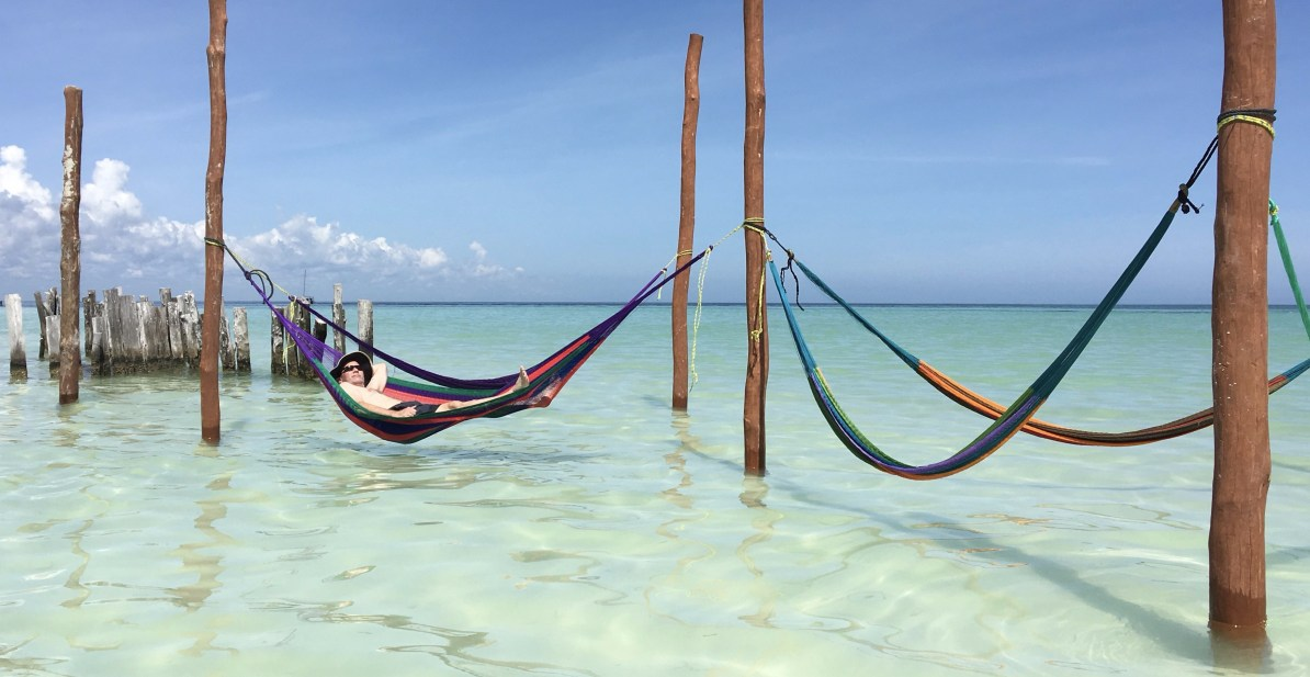 Hammocks strung over the shallow, clear ocean on Holbox Island
