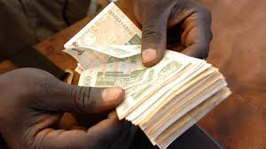 A man counting money in Sudan (source: www.cafod.org.uk)