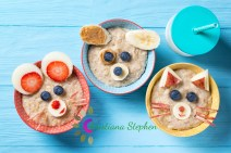 Funny bowls with oat porridge with cat, dog and mouse faces made of fruits and berries, food for kids idea, top view, blue wooden background
