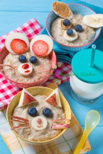 Funny bowls with oat porridge with cat, dog and mouse faces made of fruits and berries, food for kids idea on blue wooden background