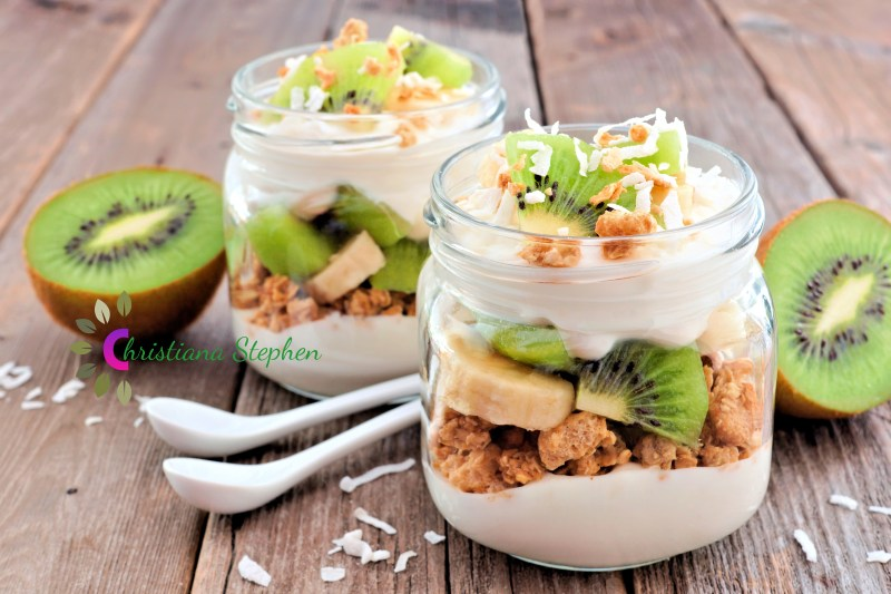 Kiwi, banana, coconut parfaits in mason jars on rustic wood