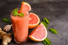 Grapefruit smoothie with ginger root and honey in a glass jar