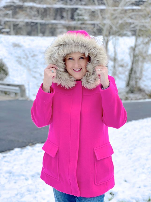 A woman in the snow with a bright pink coat with a faux fur hood