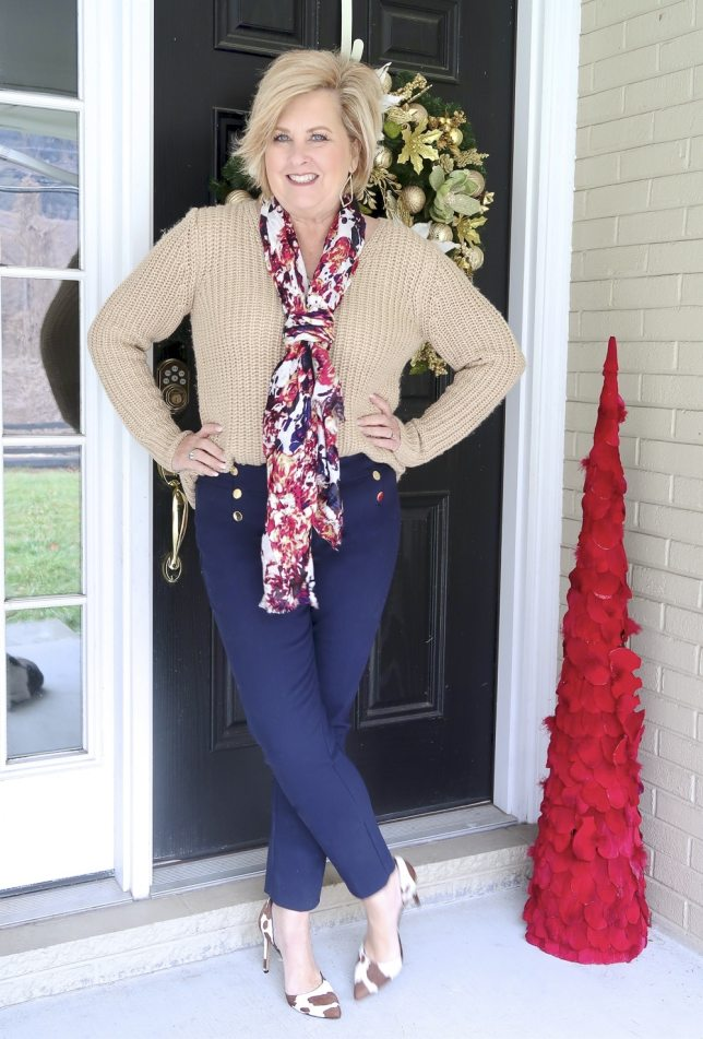 A gold v-neck sweater and navy pants worn by Fashion Blogger 50 Is Not Old